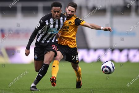 Newcastle's Joe Willock, left, is challenged by Wolverhampton Wanderers' Joao Moutinho during the English Premier League soccer match between Newcastle United and Wolves at the St James' Park stadium in Newcastle, England