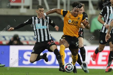 Stock Photo of Wolverhampton Wanderers' Joao Moutinho, right, is challenged by Newcastle's Miguel Almiron during the English Premier League soccer match between Newcastle United and Wolves at the St James' Park stadium in Newcastle, England