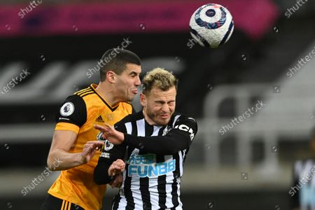 Wolverhampton Wanderers' Conor Coady, left, jumps for a header with Newcastle's Ryan Fraser during the English Premier League soccer match between Newcastle United and Wolves at the St James' Park stadium in Newcastle, England