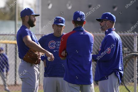 Chicago Cubs manager David Ross, right, talks to pitcher Jake Arrieta, left, during the team's spring training baseball workout in Mesa, Ariz