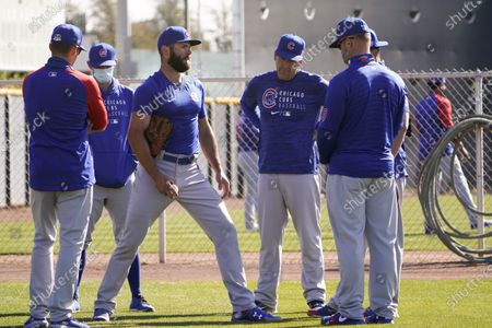 Chicago Cubs pitcher Jake Arrieta, center, is surrounded by coaches as he talks to manager David Ross, right, during the team's spring training baseball workout in Mesa, Ariz