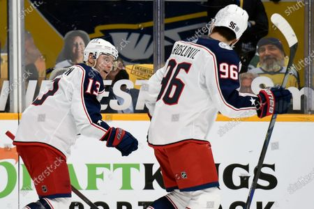 Columbus Blue Jackets right wing Cam Atkinson (13) and center Jack Roslovic (96) skate to the bench after Atkinson scored a goal against the Nashville Predators during the first period of an NHL hockey game, in Nashville, Tenn