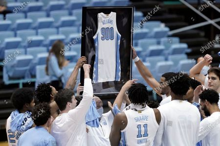 Stock Picture of North Carolina coach Roy Williams holds a framed jersey presented by the team following Williams' 900th career win, a 78-70 win over Florida State in an NCAA college basketball game in Chapel Hill, N.C