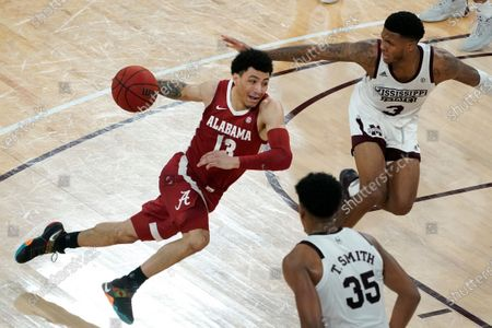 Alabama guard Jahvon Quinerly (13) drives between Mississippi State guard D.J. Stewart Jr. (3) and forward Tolu Smith (35) during the second half of an NCAA college basketball game in Starkville, Miss