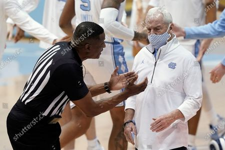 Stock Image of An official speaks with North Carolina head coach Roy Williams during the first half of an NCAA college basketball game against Florida State in Chapel Hill, N.C