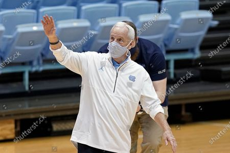 North Carolina head coach Roy Williams waves after being presented with a framed jersey commemorating Williams' 900th career win following an NCAA college basketball game against Florida State in Chapel Hill, N.C