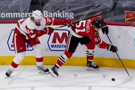 Chicago Blackhawks defenseman Ian Mitchell, right, controls the puck against Detroit Red Wings defenseman Jon Merrill during the first period of an NHL hockey game in Chicago