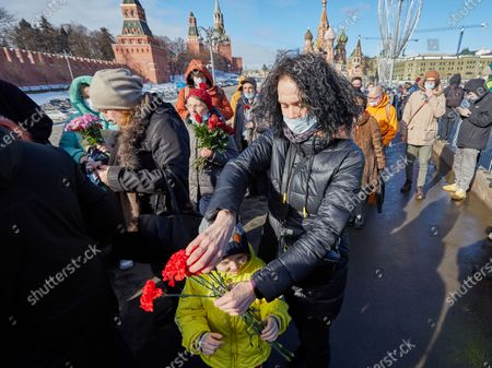 Mother and kid sharing flowers during the memorial.More than 10 thousand people took part in the memory of Boris Nemtsov on the sixth anniversary of the murder of the politician. Among them are former Prime Minister Mikhail Kasyanov, politicians Ilya Yashin, Dmitry Gudkov, Grigory Yavlinsky and Yulia Galyamina, political prisoners Konstantin Kotov and Anna Pavlikova, and Yulia Navalnaya.