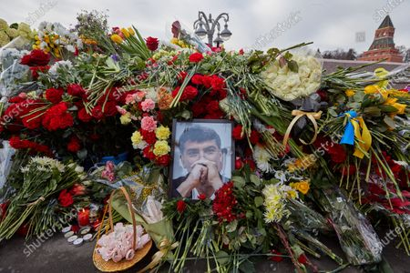 Stock Image of Flowers seen with the portrait of the murdered politician, Boris Nemtsov during the memorial.More than 10 thousand people took part in the memory of Boris Nemtsov on the sixth anniversary of the murder of the politician. Among them are former Prime Minister Mikhail Kasyanov, politicians Ilya Yashin, Dmitry Gudkov, Grigory Yavlinsky and Yulia Galyamina, political prisoners Konstantin Kotov and Anna Pavlikova, and Yulia Navalnaya.