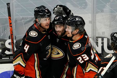 Anaheim Ducks center Adam Henrique, center, celebrates his goal with defenseman Cam Fowler, left, and right wing Carter Rowney during the third period of an NHL hockey game against the Vegas Golden Knights, in Anaheim, Calif. The Golden Knights won 3-2 in overtime