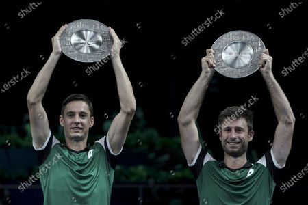 Joran Vliegen (L) and Sander Gille (R) of Belgium hold their trophies after winning their men's doubles finals match against Matthew Ebden and John-Patrick Smith of Australia at the Singapore Tennis Open ATP 250 held at the OCBC Arena in Singapore, 28 February 2021.