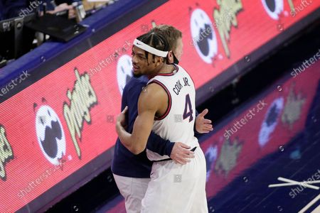 Gonzaga guard Aaron Cook (4) hugs head coach Mark Few as the senior leaves the court during his last home game during the second half of an NCAA college basketball game against Loyola Marymount in Spokane, Wash