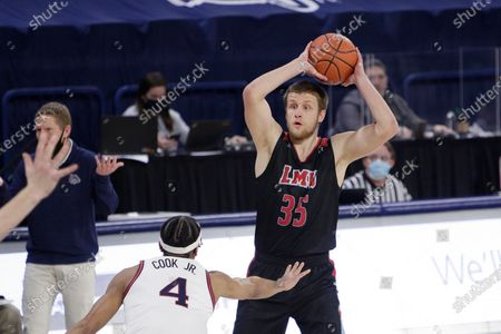 Loyola Marymount forward Ivan Alipiev (35) handles the ball while pressured by Gonzaga guard Aaron Cook (4) during the first half of an NCAA college basketball game in Spokane, Wash