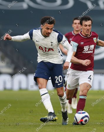 Stock Image of Tottenham's Dele Alli, left, controls the ball under pressure from Burnley's Jack Cork during an English Premier League soccer match between Tottenham Hotspur and Burnley at the Tottenham Hotspur Stadium in London, England, Sunday, Feb. 28. 2021