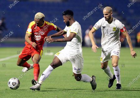 Al-Qadisiyah's player Carolus Andria (L) in action against Al-Ittihad's Muhannad Al-Shanqeeti (C) and Karim El Ahmadi (R) during the Saudi Professional League soccer match between Al-Qadisiyah and Al-Ittihad at Prince Mohammed Bin Fahd Stadium, in Dammam, Saudi Arabia, 28 February 2021.
