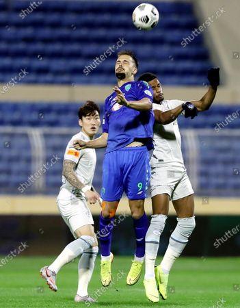 Stock Image of Al-Fateh's player Mitchell Te Vrede (C) in action against Al-Hilal's Ali Al-Boleahi (R) and Hyun Soo Jang (L) during the Saudi Professional League soccer match between Al-Fateh and Al-Hilal at Prince Abdullah bin Jalawi Stadium, in Al-Hasa, Saudi Arabia, 28 February 2021.