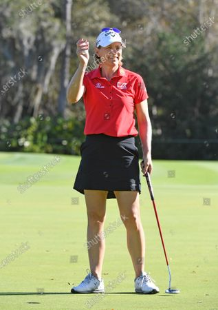 Annika Sorenstam of Sweden dressed in red and black waves to fans on the putting green during the final round of the Gainbridge LPGA golf tournament, in Orlando, Fla