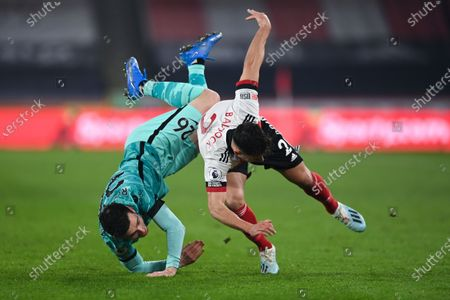 Liverpool's Andrew Robertson, left, and Sheffield United's George Baldock fall to the ground during the English Premier League soccer match between Sheffield United and Liverpool at Bramall Lane stadium in Sheffield, England