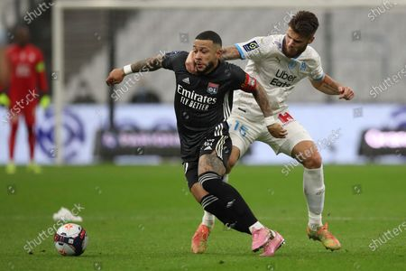 Lyon's Memphis Depay, left, is challenged by Marseille's Duje Caleta-Car during the French League One soccer match between Marseille and Lyon at the Stade Veledrome stadium in Marseille, France