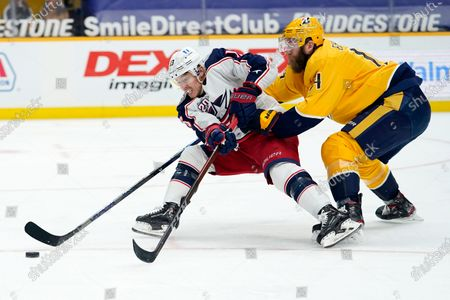 Columbus Blue Jackets right wing Cam Atkinson (13) and Nashville Predators defenseman Ryan Ellis (4) battle for the puck in the first period of an NHL hockey game, in Nashville, Tenn