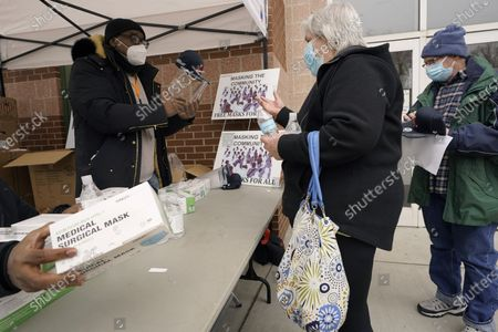 Stock Image of Volunteer Leonard Lee, of Boston, behind left, distributes masks and sanitizer to Nancy Prunier, of Shirley, Mass., center, after she received a COVID-19 inoculation at a vaccination site at the Reggie Lewis Center, in Boston