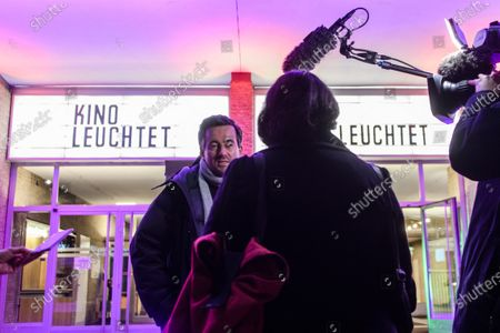Christian Schwochow gives an interview in front of the illuminated Kino International cinema on the occasion of the event 'Cinema lights up. For you' (Kino leuchtet. Fuer Dich) in Berlin, Germany, 28 February 2021, a day before the official start of the 71st Berlinale, which this year is a virtual event running from 01 to 05 March. The cinema operators event aims to draw attention for the situation of the still closed cinemas in Germany, due to restrictions of the coronavirus pandemic.