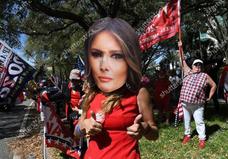 A woman wearing a Melania Trump mask rallies with others in support of former President Donald Trump outside the 2021 Conservative Political Action Conference at the Hyatt Regency where Trump is scheduled to speak.