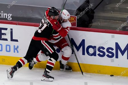 Chicago Blackhawks' Ian Mitchell, left, and Detroit Red Wings' Darren Helm battle for the puck during the second period of an NHL hockey game in Chicago