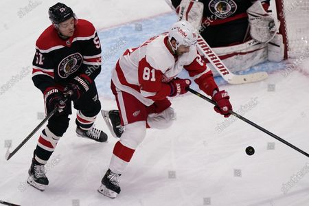 Detroit Red Wings' Frans Nielsen, right, tries to control the puck against Chicago Blackhawks' Ian Mitchell during the third period of an NHL hockey game in Chicago