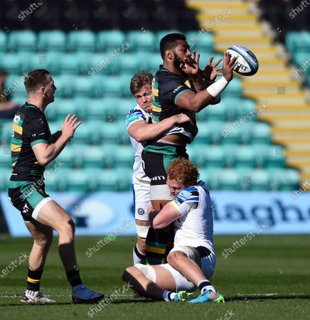 Taqele Naiyaravoro of Northampton Saints offloads the ball after being double-tackld by Tom Ellis and Miles Reid of Bath Rugby