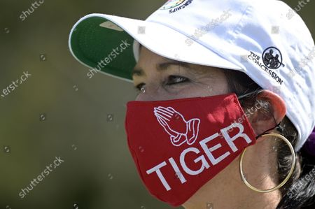 Spectator Desiree Kapica, of Sarasota, Fla., watches the action at the 12th green while wearing a homemade mask in honor of golfer Tiger Woods during the final round of the Workday Championship golf tournament, in Bradenton, Fla