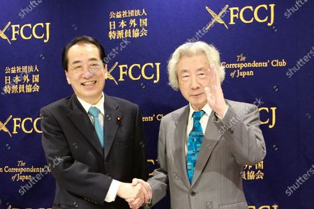 """Japan's former Prime Ministers Junichiro Koizumi, right, and Naoto Kan shake hands during their joint press conference on the theme of """"Ten years after Fukushima - Nuclear power in Japan"""" in Tokyo"""