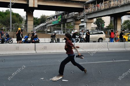 An anti-government protester is seen throwing a item to riot police policers during a rally in Bangkok as marching toward the residence of Thailand's Prime Minister Prayut Chan-O-Cha on February 28, 2021 in Bangkok, Thailand.  (Photo by Vachira Vachira/NurPhoto)