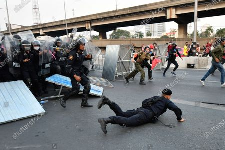A riot police officer falls while face off against anti-government protesters during a rally in Bangkok as marching toward the residence of Thailand's Prime Minister Prayut Chan-O-Cha on February 28, 2021 in Bangkok, Thailand.  (Photo by Vachira Vachira/NurPhoto)