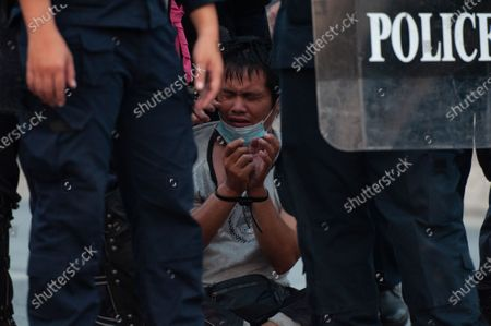 Stock Photo of An anti-government protester is seen detained by riot police officers during a rally in Bangkok as marching toward the residence of Thailand's Prime Minister Prayut Chan-O-Cha on February 28, 2021 in Bangkok, Thailand.  (Photo by Vachira Vachira/NurPhoto)