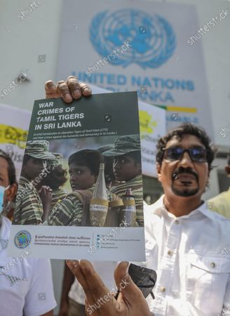 A member of an organization calling itself the 'International People's Organisation of Sri Lanka' holds a cover of a document detailing war crimes committed in the island by the Liberation Tigers of Tamil Eelam (LTTE), during a protest in front of the United Nations office in Colombo, Sri Lanka, 01 March 2021.  A group of Buddhist monks and members of the 'International People's Organisation of Sri Lanka' protested the moves by the United Nations Human Rights Council (UNHRC) which is currently holding its 46th regular session in Geneva to introduce resolutions imposing sanctions on the island nation for 'war crimes and human rights violations'. The UNHRC is to introduce another resolution on Sri Lanka, based on a report by UNHRC Commissioner Michelle Bachelet, which calls for an International Criminal Court investigation into Sri Lanka's near 30-year-old separatist conflict that ended in 2009 and sanctions against top military personnel and others accused of war crimes. The Sri Lankan government has firmly denied such violations and has urged member countries to defeat this 'politically biased' resolution.