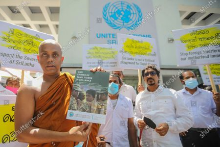 A Sri Lankan Buddhist monk holds a cover of a document detailing war crimes committed in the island by the Liberation Tigers of Tamil Eelam (LTTE), during a protest in front of the United Nations office in Colombo, Sri Lanka, 01 March 2021.  A group of Buddhist monks and members of the 'International People's Organisation of Sri Lanka' protested the moves by the United Nations Human Rights Council (UNHRC) which is currently holding its 46th regular session in Geneva to introduce resolutions imposing sanctions on the island nation for 'war crimes and human rights violations'. The UNHRC is to introduce another resolution on Sri Lanka, based on a report by UNHRC Commissioner Michelle Bachelet, which calls for an International Criminal Court investigation into Sri Lanka's near 30-year-old separatist conflict that ended in 2009 and sanctions against top military personnel and others accused of war crimes. The Sri Lankan government has firmly denied such violations and has urged member countries to defeat this 'politically biased' resolution.