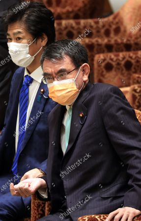Japanese Administrative Reform Minister Taro Kono (R) and Health Minister Norihisa Tamura (L) listens to a question at Lower House's budget committee session at the National Diet in Tokyo on Monday, March 1, 2021.