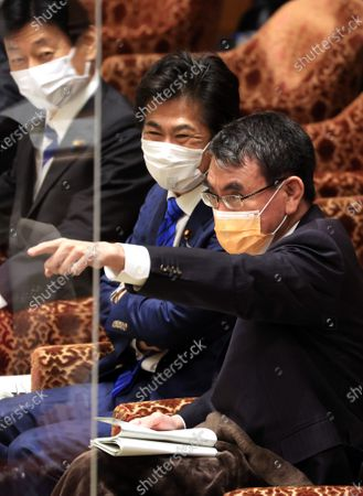 Japanese Administrative Reform Minister Taro Kono (R) recats to an opposition lawmaker while Health Minister Norihisa Tamura (C) and Fiscal Policy Minister Yasutoshi Nishimura (L) look on at Lower House's budget committee session at the National Diet in Tokyo on Monday, March 1, 2021.