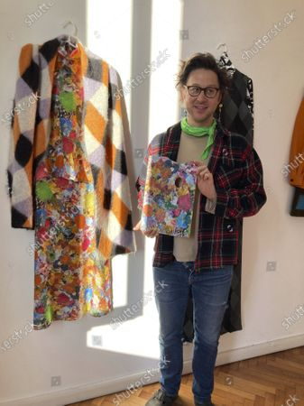 Stock Image of Milan-based Austrian fashion designer Arthur Arbesser, poses in his studio holding a painter's pallet that he picked up at a flea market, and which inspired the signature print for his Fall 2021 collection of 25 looks, in Milan, Italy, . Arbesser decided against a runway show in this digital era, instead focusing his creative energies to make a collection from revitalized textiles from his archives that he had printed over, and experimenting with other artisanal techniques with his small team