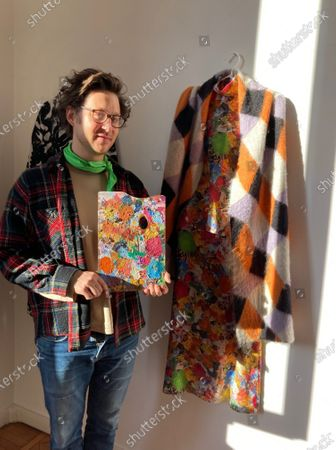 Milan-based Austrian fashion designer Arthur Arbesser, poses in his studio holding a painter's pallet that he picked up at a flea market, and which inspired the signature print for his Fall 2021 collection of 25 looks, in Milan, Italy, . Arbesser decided against a runway show in this digital era, instead focusing his creative energies to make a collection from revitalized textiles from his archives that he had printed over, and experimenting with other artisanal techniques with his small team