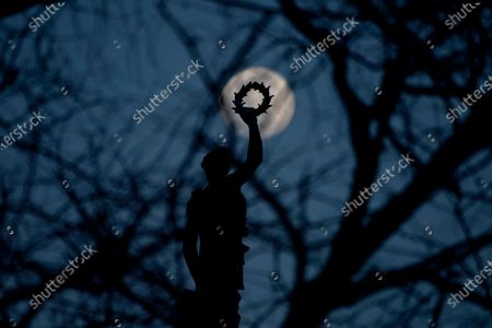 Waxing moon is seen behind trees and and a statue atop the Peggy Stewart Monument, in Baltimore, Md. The monument honors the Peggy Stewart, a brigantine ship that was burned when it arrived at the port of Annapolis in October 1774, with a cargo of tea, which violated a boycott on a highly controversial tax imposed by Britain
