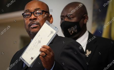 Stock Photo of Reggie Wood, left, stands with civil rights lawyer Ben Crump, while showing a letter, believed to be a confession from his cousin, former NYPD officer Ray Wood, during a press conference, at the Malcolm X and Dr. Betty Shabazz center in New York. Wood, an undercover NYPD officer in the 1960s, confessed in a deathbed declaration letter that he conspired with NYPD and the FBI to undermine the legitimacy of Malcolm X and other leaders of the civil rights movement