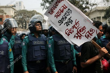 An activist from the left parties holds a placard as she attends a protest march during a demonstration in Dhaka, Bangladesh on March 01, 2021, following the death of a Bangladeshi writer Mustak Ahmed in prison, who was arrested under the digital security act.