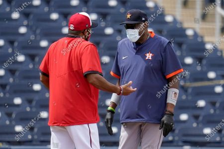 Washington Nationals manager Dave Martinez, left, and Houston Astros manager Dusty Baker talk before the start of a spring training baseball game, in West Palm Beach, Fla