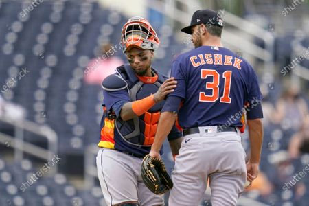 Houston Astros pitcher Steve Cishek (31) gets a pat on the shoulder from catcher Martin Maldonado after giving up a home run to Washington Nationals' Ryan Zimmerman during the third inning of a spring training baseball game, in West Palm Beach, Fla
