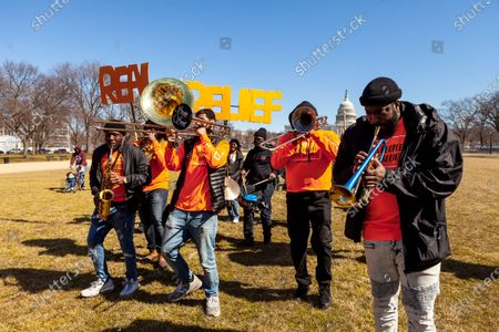 Too Much Talent Band accompanies protesters at the Real People Real Relief rally on a short march in front of the Capitol.