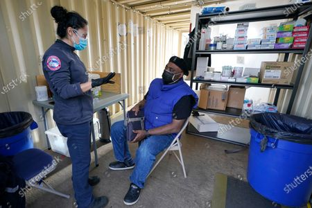 Stock Image of Wendy Benitez, left, an EMT with American Medical Response, talks with James Thomas, right, after she gave him the first dose of the Moderna COVID-19 vaccine, at a City of Seattle community COVID-19 testing and vaccination clinic in Seattle's Rainier Beach neighborhood. Seattle Mayor Jenny Durkan announced Monday that the city's COVID-19 vaccination efforts would be expanding in the coming weeks as more doses become available, including the use of the events center at Lumen Field - the home of the NFL football Seattle Seahawks and the MLS soccer Seattle Sounders - as a mass vaccination site with the capacity to deliver thousands of doses every day