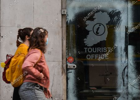 Stock Photo of Two young women walk by a closed Turism Office in Dublin city center during Level 5 Covid-19  lockdown. On Monday, March 1, 2021, in Dublin, Ireland.