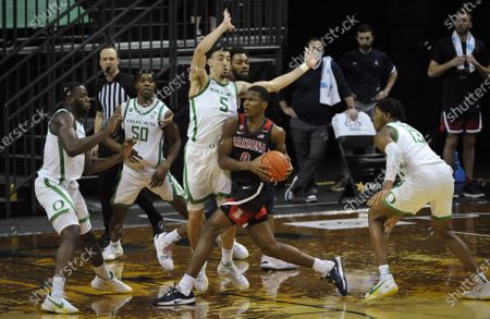 Arizona guard Bennedict Mathurin (0) looks to pass as he is defended by Oregon forward Eugene Omoruyi (2), forward Eric Williams Jr. (50), guard Chris Duarte (5) and forward Chandler Lawson (13) during the second half of an NCAA college basketball game, in Eugene, Ore